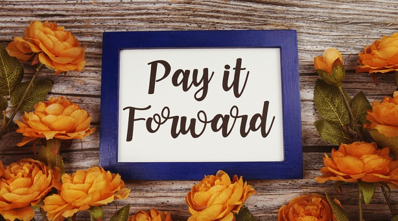 Pay it forward typography text with flower decoation on wooden background
